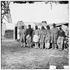 """[Bermuda Hundred, Va. African-American teamsters near the signal tower], 1864.  Photograph from the main eastern theater of the war, the Army of the James, June 1864-April 1865. Shows group of seven """"contrabands"""" dressed in old Union uniforms standing in front of a wagon and shack."""