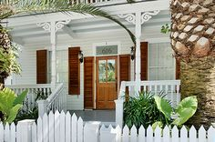 Deep porches, red shutters, gingerbread trim, extraordinary date palm trees off-set this beautiful Victorian home on Caroline Street, Key West.