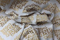 Description Gold embroidered medallions on a flaxen natural background.