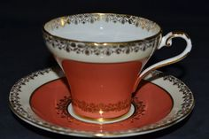 Beautiful soft orange corset teacup and saucer by Aynsley accented with gold trim around the top and bottom of the cup.