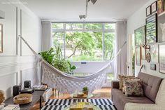 Com vista para o verde, a sala desse apê conta com rede de balanço feita artesanalmente.