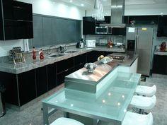 A cozinha não é integrada, mas tem conta com uma bancada gourmet de vidro verde dá mais leveza à decoração preta.