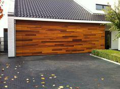Een #houten #garagedeur uitgevoerd in de houtsoort Red Cedar, behandeld met een olie. De #garagedeur is geïntegreerd in de gevel van de woning.