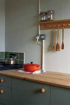 A single pine shelf runs the length of the kitchen, and, on one end, features a row of Shaker pegs. The countertops are also pine, styled here with a Le Cruset Flame Dutch Oven, bamboo utensils, and Le Parfait Super Jars.