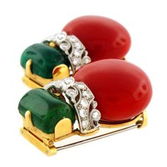 Seaman Schepps Oxblood Coral Emerald & Diamond 1940s Dress Clips $18,500  Very rare Seaman Schepps 1940s-era dress clips with magnificent oxblood coral (22cm diameter ea.), emerald cabochons (approx 6cts ea.) and white diamond accents set in 14K yellow gold. Signed Seaman Schepps. – Circa 1940s