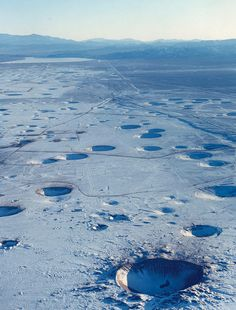 dequalized After 800 nuclear tests from 1951 and 1992, this is the view over the Nevada Test Site (formerly known as the Nevada Proving Grounds).   All the craters seen in the photograph are from below ground tests and are collapse features from subsidence into the largely vaporized detonation zone.