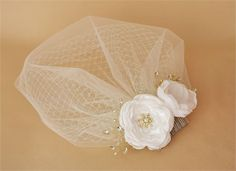 This listingis for a lovely vintage style birdcage veil and a handmade satin flower fascinator. The veil is made with 2 layers of netting -   under layer is 9 long russian netting for a retro look   over layer is made with illusion netting for a modern twist. The illusion netting part is cut slightly larger and longer for a shape and softer edge.    The veil can be made in WHITE, IVORY and CHAMPAGNEcolors. it is set on to a silver tone wire hair comb. I will include 2 extra bobby pins with…