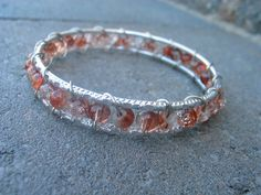 Wire wrapped bangle silver colored bracelet with clear white and brown frosted beads.. $12.00, via Etsy.