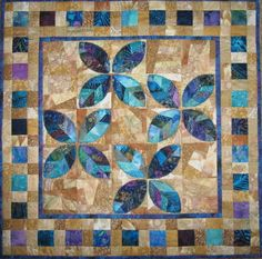 """Blue Leaves on Sand.  24 X24 inches   Leaves were pieced from scraps then cut into leaf shapes.  Raw edge appliqued to a """"crazy quilt"""" pieced background, using a squiggly pattern and gold thread.  I used golden colored scraps for the background.  Designed and created by Denise Enberg"""