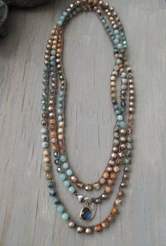 Earthy mix of semi precious stones, freshwater pearls, and Czech glass with a sterling silver charm and findings. Wear it with earthtones/ neutrals like beige, gray, and oatmeal.....    Wear it with the dangles in the front with a V-neck top or with the closure in the back with crew or scoop necks. Looks amazing layered with other wraps and necklaces you may already own or with ones available in my shop, as shown. **3rd & 4th pics show this necklace layered with 2 similar Topanga necklaces…