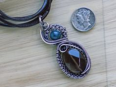 Smoky Quartz Apatite Copper wire Pendant Wire Wrapped, Oxidized, Handcrafted by me.  Made with Copper wire ( aides in circulation ), a Pretty Faceted Smoky Quartz Oval bead ( grounding, balancing...overcome negativity ) and a round Teal Blue Apatite bead ( communication, self expression )  This pendant is about 2 tall and is strung on a brown leather cord tied for size adjust ability.  I love following Nicole Hannas awesome wire tutorial to make this design.  Take a look at both my shops…
