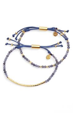 Accessorizing with this set of two slender bracelets that feature a glistening hammered-metal bar and glossy rondelles.