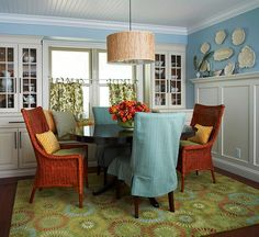 Vibrant Hues-The red, orange, and blue in this fresh green rug draw together all the tones in this traditional and elegant dining room.    Why It Works  -- The rug becomes the foundation of the room, allowing the other colored elements to be featured beautifully.  -- To add unexpected color to the room, red wicker and blue slipcovered chairs are pulled up to the table