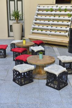 Spool coffee tables with milk crate seats in front of a herb wall