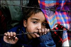 A young boy peers through the barbed wire fence of a refugee camp in Muzaffarabad, Pakistan, in the wake of the South Asian earthquake of 2005.