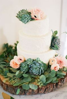 A three-tiered white wedding cake decorated with greenery, succulents, peonies, ranunculus, and dahlias   http://Brides.com