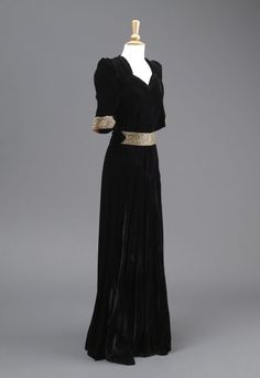 Profile of the Black Velvet Evening Dress, the full length skirt is bias cut. 1930-32 Black Velvet Evening Dress 1930-32 The evening dress of black velvet has a ruched sweetheart neckline and an intricately cut bodice. The dress has a high front with elbow length sleeves. It is fastened with four buttons. The simple but striking decoration found on the cuffs and waistband, is gold lame, with plastic gemstones. The full length dress has a low v-neck and a gathered panel at the back.