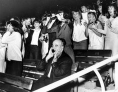 A man covers his ears as 18,000 screaming fans react to The Beatles in the Hollywood Bowl, California, during their U.S. concert tour on Aug...