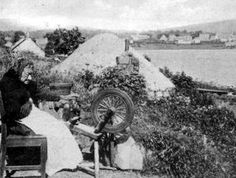 Old photograph of an old crofter hand spinning wool outside her thatched cottage on Isle of Skye, Scotland