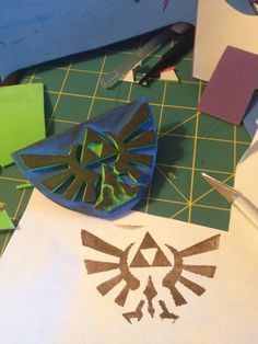 Legend of Zelda stamp, made with self adhesive foam sheet. Trace the Hylian shield over one pice of self adhesive foam then cut with an X-acto knife for more precision. Then remove the protective paper and glue on to another piece of foam sheet. Do this once or twice depending on how deep you want the stamp to be. Use acrylic paint, if you want a more faded effect then dilute the paint with water.