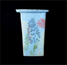 Vintage Carol Wynne Morris rare pottery slab vase from the Conwy Pottery in Wales. Decorated with common garden flowers and speckled blue matte glaze on a white earthenware body. The base of the vase is stamped CONWY POTTERY in a black circle. Very unusual rare design by Wynne. Lovely display item. Please note: The vase is in a slightly lighter blue than the pictures listed above.   Medium: White Earthenware - Studio Pottery Matt Blue - Flower Design Glazes.   Dated: 1970-80s   Condition…
