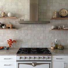 This pearly white kitchen is elegant yet subtle. And that white gas range is too die for!