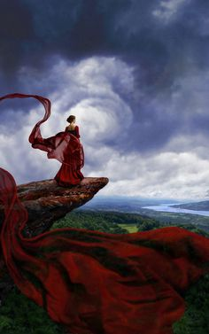 Woman on a cliff with a dress pourpe veils of which float in winds
