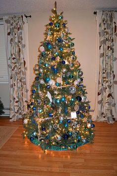 Blue and White Christmas Tree in-between two windows instead of in front of them