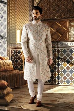 BOTTLE GREEN RAW SILK SHERWANI The unique concept of sherwani over kurta is a mark of exquisite style.Made in raw silk this bottle green sherwani with heavy embroidery detailing is bound to make you the man of the evening! Sherwani For Men Wedding, Wedding Dresses Men Indian, Groom Wedding Dress, Wedding Outfits For Groom, Sherwani Groom, Wedding Men, Wedding Suits, Punjabi Wedding, Indian Weddings