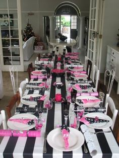 Black and white striped table cloths and spash of pink.