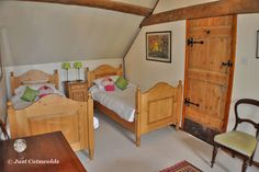 The lovely twin bedroom with warm wooden beds has a lovely calm feel.                              #Cotswolds #holiday #luxury #rental