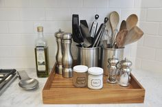 Use silver containers to hold your most-used kitchen utensils, and leave your frequently-used spices on the counter, too. Keep it all organized on a tray that you can move in a pinch.