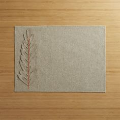 This rustic-chic, natural placemat is crafted entirely of wool felt with a striking appliqué of a dimensional, laser-cut leaf.  The soft neutral hue is accented with a pop of orange embroidery securing the leaf to placemat, with overlock-stitched edging for durability. 100% wool feltSpot clean onlyMade in India.