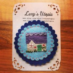 Sweet little Crofters cottage brooch handmade using wool felt and embroidered. Measures roughly 2 inches in dia and presented on a Lexys Utopia card