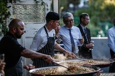 Cnk Catering chefs cooking paella on the Richmond Rowing Club deck for a wedding!