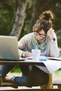 Beautiful young student with glasses with notes and laptop writing on a park. by Eduard Bonnin