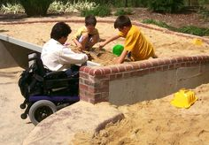 Universally designed sand play, can roll up to it, climb on it or sit on berm edge.