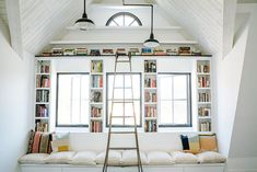 Frame the windows with books to create a reading nook. The combination of color and natural light adds major impact to a whitewashed space. Chic library ladder is the bomb.