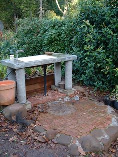 Concrete outdoor sink with cement legs and integrated drain in vegetable garden.