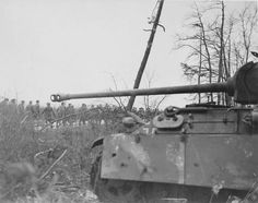 A Panther Ausf G sitting idle as large column of unidentified soldiers pass by on a road