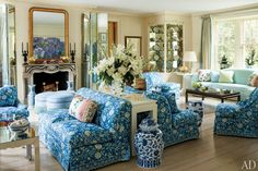 A Brunschwig & Fils floral fabric brightens the Southampton living room, where a vintage Karl Springer console is flanked by a pair of matching settees. Great way to separate a large room.