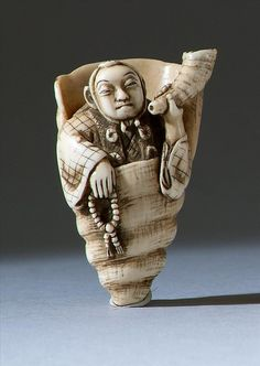 """IVORY NETSUKE Meiji Period In the form of a priest inside a conch shell. Signed """"Tomozan"""". Length 2"""" (5 cm)."""