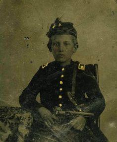 Civil War Era child soldier in uniform sitting holding revolver.