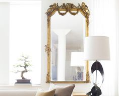 The Interior Designer Jon Call showcases how to use select antique pieces as this big floor mirror and not overwhelm.