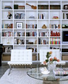 White Barcelona Chairs in a elegantly curated library...my dream reading space esp. with large arching french windows across the way withs sunlight streaming in.