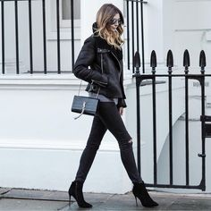 Black aviator jacket, ripped skinny jeans, YSL tassel bag, heeled ankle boots, all black outfit