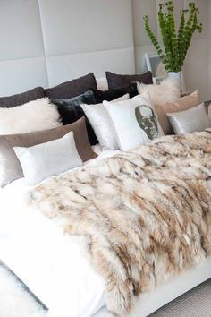 Layered Luxe- use classic crisp white sheets and duvet, cover with faux fur blanket, add 3 rows of throw pillows in various textures starting from back (largest) euro sham in charcoal, middle (medium) 3 faux fur pillows 2 white flanking 1 black, front (small) various shaped metallic and 1 statement print or typefront pillow front and center
