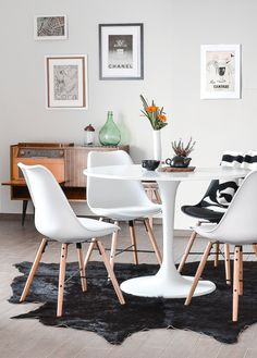black white and wood- love this dining area with midcentury modern table and chairs and hide rug