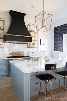 The ultimate guide on styling open kitchen shelves...    kitchen-white-marble-calcutta-gold-open-shelves-gold-black-vent-hood-blue-gray-cabinets-shaker-style-black-chevron-tile-subway-white-backsplash-decor-ideas-32-of-32