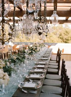 We love the use of long tables. With garden style arrangements and the different styles of chandeliers, this set-up is classic romance.
